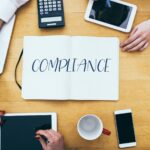 Compliance headline on paper notebook at small business office desk with young adult workers