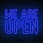 We are open - blue neon light word on brick wall background
